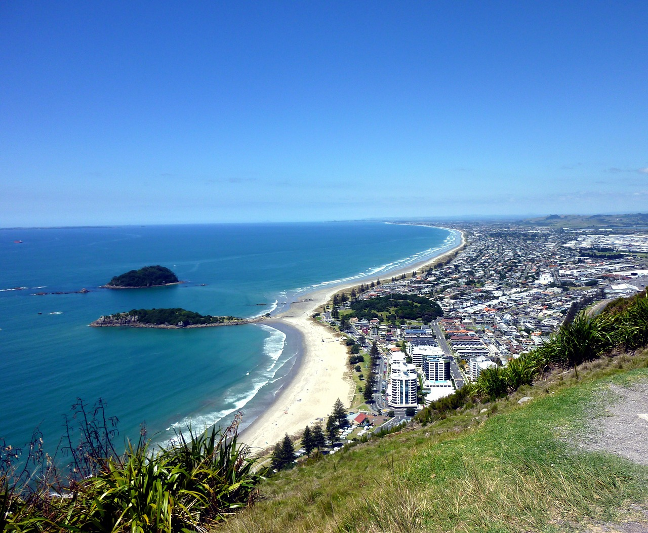 View of Maunganui beach, and Moturiki and Motuotau Islands from the top of Mount Maunganui on a calm day.
